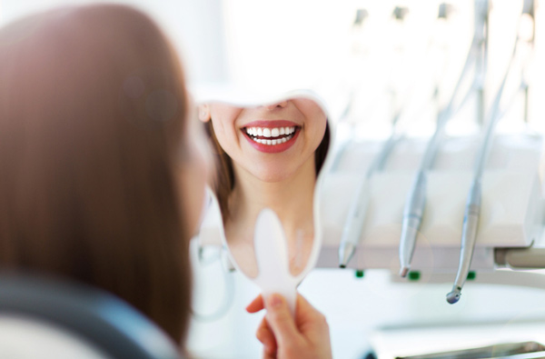 Woman looking at her smile in a mirror at South Austin Dental in Austin, TX