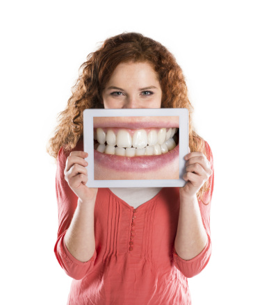 Woman holding a new smile photo over her face