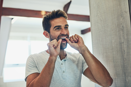 Man flossing his teeth before a checkup at South Austin Dental in Austin, TX
